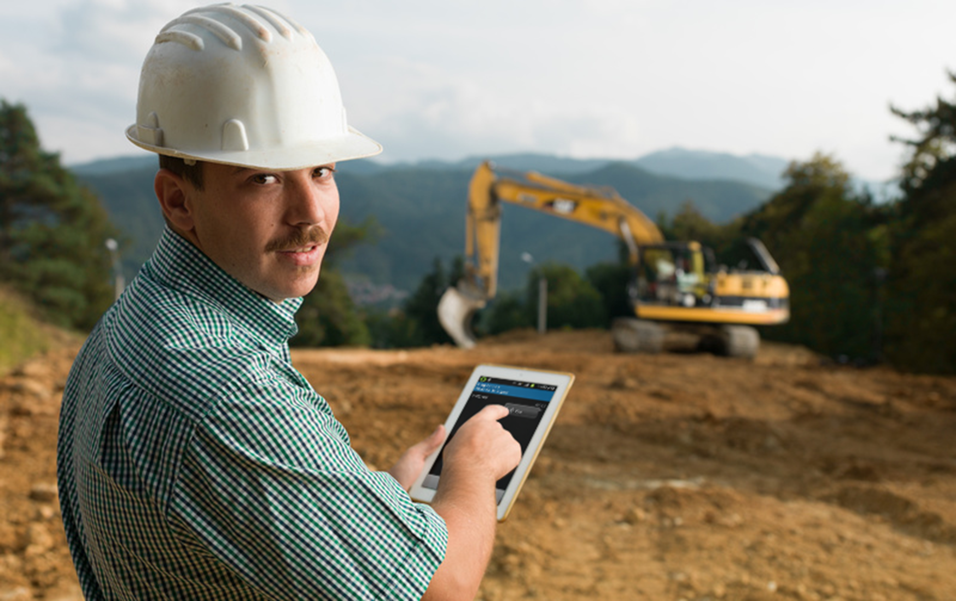 construction worker with a tablet in front of an excavator